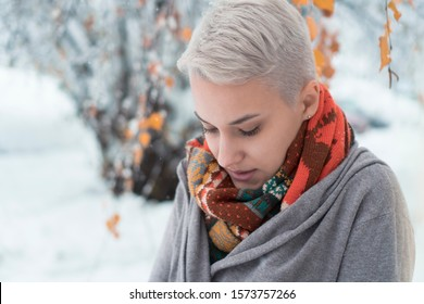 Beautiful young short white hair woman standing outdoors on cold winter day. Serious girl with colorful scarf outside in park looking down. Snow day. Winter fashion.