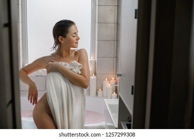 Beautiful young short-haired, dark-haired woman in a white bath towel in the bathroom after bath.