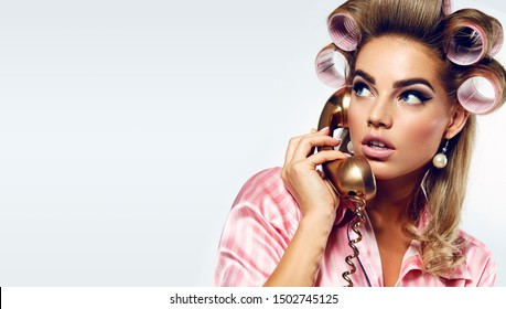 A beautiful young showy girl with bright pin-up make-up speaks on a golden dial telephone in pink striped silk pajamas and pink curlers.