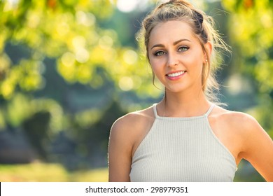 Beautiful young single adult blonde female active outdoor portrait with perfect skin and teeth smiling