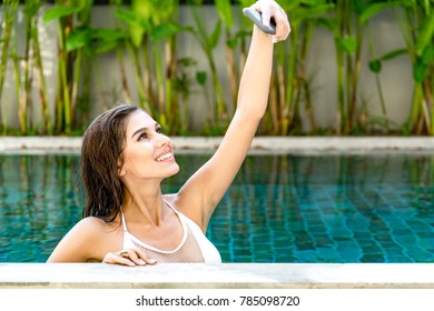 Beautiful young single white woman in pool. Using mobile phone for selfie, wearing white bikini. Connected world concept.