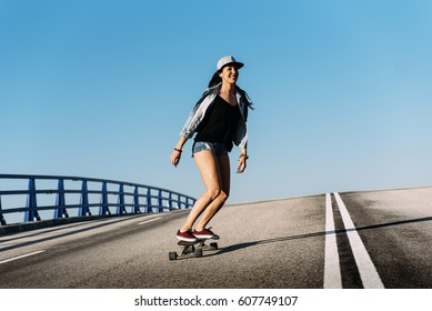 Beautiful young skater woman riding on her longboard in the city.