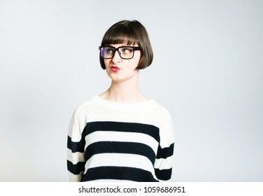 beautiful young skeptical woman, short haircut, wears a sweater, studio photo on a background
