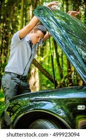 beautiful young slender man stands next car hood open background summer green park