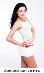 beautiful young slim brunette woman against studio background
