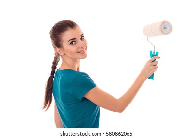 beautiful young slim builder girl makes renovations with paint roller isolated on white background
