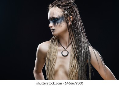 A beautiful young slim girl with avant-garde blue make-up and a hairstyle of cornrows, covers her topless breast with a rope that hangs on her neck. Conceptual, creative, commercial design.