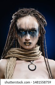 A beautiful young slim girl with avant-garde blue make-up and a hairstyle of cornrows, covers her breast with a rope that hangs on her neck. Conceptual, creative, commercial design.