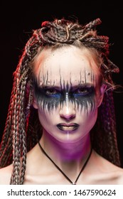 A beautiful young slim girl with creative make-up and a hairstyle of cornrows, covers her topless breast with with her hands. She lighted from below with violet light. Conceptual, commercial, design.