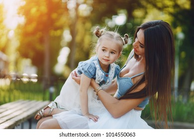 a beautiful young slim and long-haired mom sitting in the park with her little daughter