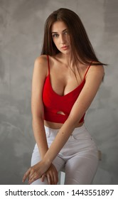 Beautiful young slim sexy woman in red in studio on a grey background