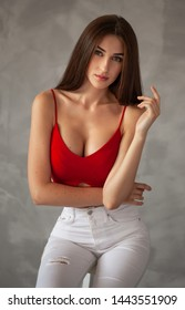 Beautiful young slim sexy woman in red in studio on a gray background