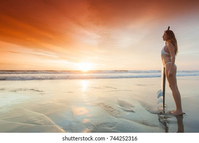 A beautiful young slim sporty woman in bikini with a surfboard is standing at ocean beach at sunset