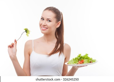 Beautiful young slim woman is eating healthy salad. She is standing and holding plate with fork. The lady is looking forward and smiling. Isolated and copy space in right side