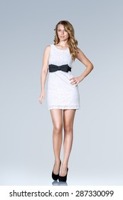 Beautiful young slim woman in white mini dress full body studio portrait