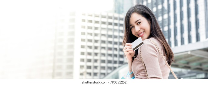 Beautiful young smiling Asian woman going to shopping in the city with credit card, panoramic banner with copy space