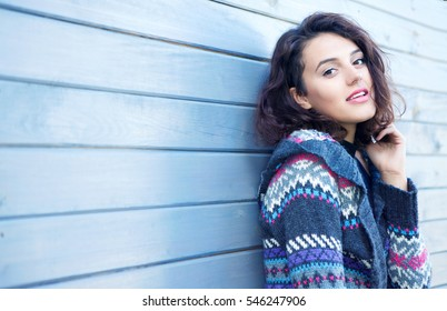 Beautiful young smiling brunette woman with wearing knitted nordic print cardigan on a grey wooden background. Winter fall fashion beauty concept.