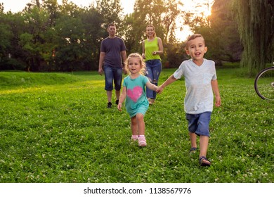 Beautiful young smiling children walking with parents in park