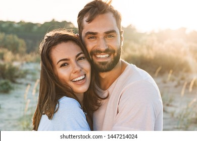 Beautiful young smiling couple spending time at the beach, hugging