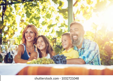 Beautiful young smiling family of four with dog having picnic at a vineyard.