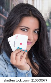 Beautiful young smiling girl holding ace cards from a deck of cards