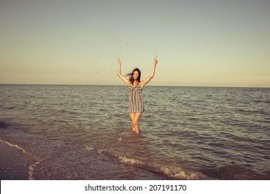 Beautiful young smiling girl splashing the water in the sea