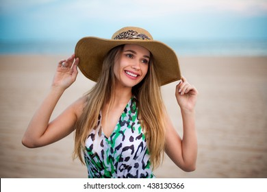 Beautiful young smiling girl wearing a hat on the beach. Happy girl enjoying the summer time on sand beach near the ocean and holding hat on the wind at sunset time.