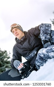 Beautiful young smiling man with snowboard enjoying a winter day.