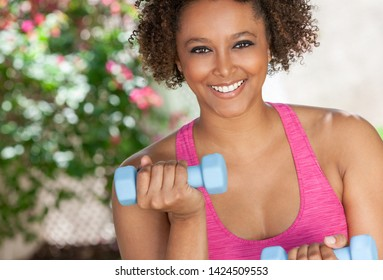 Beautiful young smiling mixed race biracial black African American woman exercising outside using weights, fitness aerobic exercising pilates.