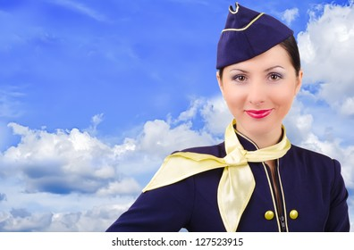 Beautiful young  smiling stewardess on a background sky
