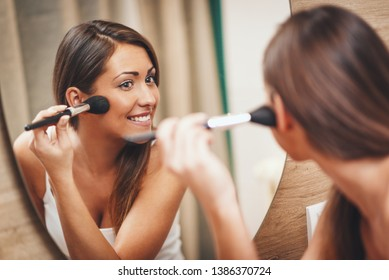Beautiful young smiling woman is applying make up in front of her bathroom mirror.