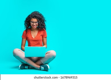 Beautiful young smiling woman in casual outfit and trendy eyeglasses sitting isolated on bright colored blue background and working on her laptop. Full length horizontal studio shot. Copy space. - Shutterstock ID 1678969315
