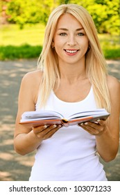 Beautiful young smiling woman dressed in white reading book, against green of summer park.