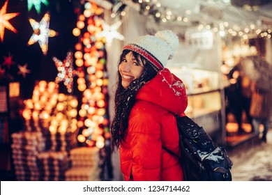 Beautiful young smiling woman enjoy snow winter time on Christmas fair in night city wearing hat and red jacket