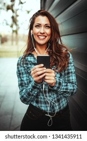 Beautiful young smiling woman enjoying the music via headphones and holding smartphone in her hands in the office district.