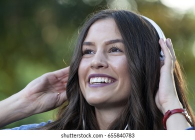 Beautiful young smiling woman enjoying and relaxing while listening to music