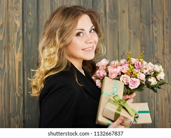 Beautiful young smiling woman with gift boxes and flowers.young woman in suit. Young business woman. Young and beautiful teacher