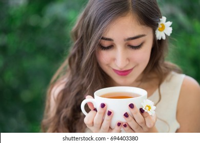 A beautiful young smiling woman with long curly hair and long eyelashes in white top and a flower in hair holding and looking down at the white cup of tea in hands, with green trees in the background