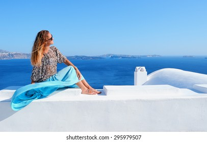 Beautiful young smiling woman in Oia town sitting on a roof of a white house on Santorini island in Greece