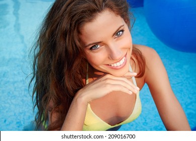 Beautiful young smiling woman in the pool