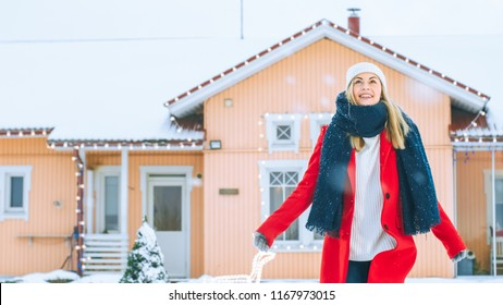 Beautiful Young Smiling Woman Rises Her Hands to the Sky at Winter Day. Girl in a Red Coat with a Scarf Enjoys Falling Snow in the Yard.