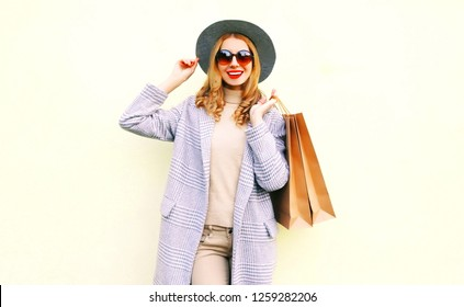 Beautiful young smiling woman with shopping bags in pink coat, round hat on wall background