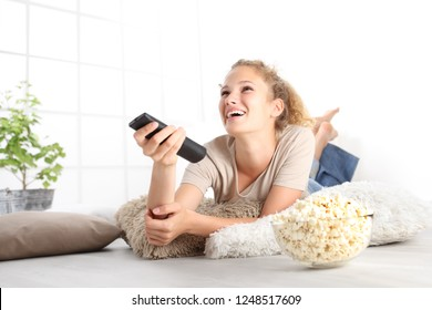 beautiful young smiling woman with tv remote control watching the television eating popcorn lying on living room wooden floor in comfortable home