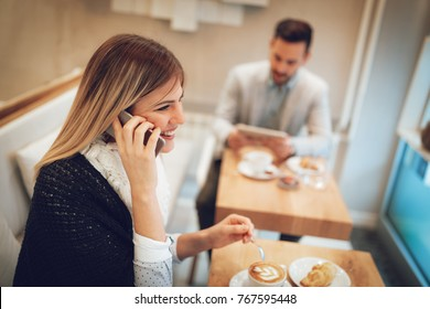 Beautiful young smiling woman using smartphone and drinking coffee in a cafe. Selective focus. Focus on businesswoman.
