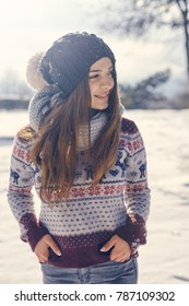 beautiful young smiling woman walking in sunny winter weather looking away