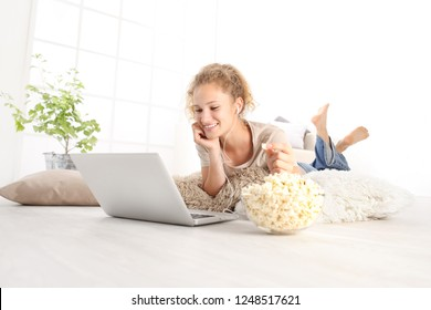beautiful young smiling woman watch a movie at the computer eating popcorn lying on living room wooden floor in comfortable home