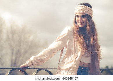 Beautiful young smiling woman. Women's clothing. Outdoors in the city. Jacket, jeans and handbag on her shoulder. Pink headband on the head. Happy and smiling outdoors. On vacation enjoying free time.