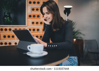 Beautiful young smiling woman working in modern coffeeshop on new creative project, happy smiling freelancer girl sitting in hipster cafe using digital tablet device working on new design for website