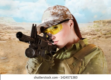 Beautiful young soldier woman in military uniform aiming at the enemy with automatic rifle M16, on desert background, close up.
