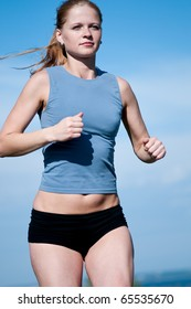 Beautiful young sport woman running over blue sky